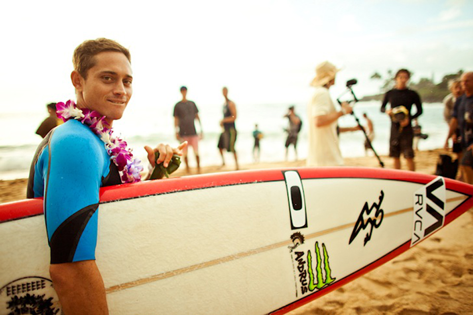 Makua Rothman carrying a surfboard on the beach