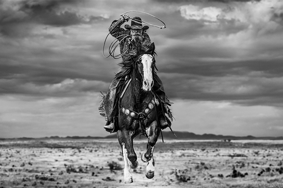 A cowboy swinging a lasso rides through the desert.