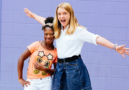 Two female Middle School participants standing close to each other and smiling