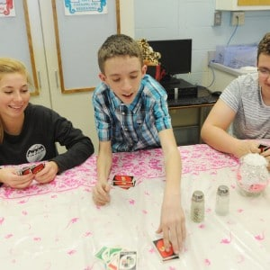 Laurie Eells, Austin Linton and Jamie Cool-Luke play a card game during a recent Peer Pals party after school at Eastern Hancock High School. (Tom Russo | Daily Reporter) Thomas J Russo