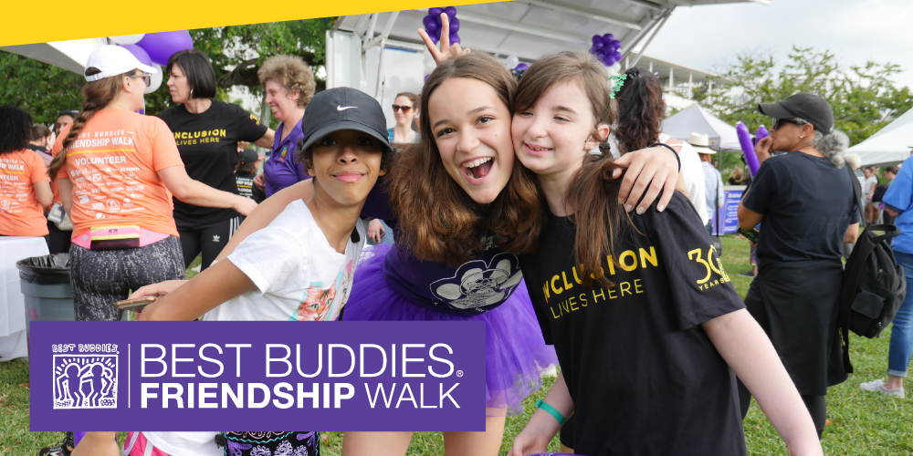 3 Best Buddies participants huddled at a Best Buddies Friendship Walk