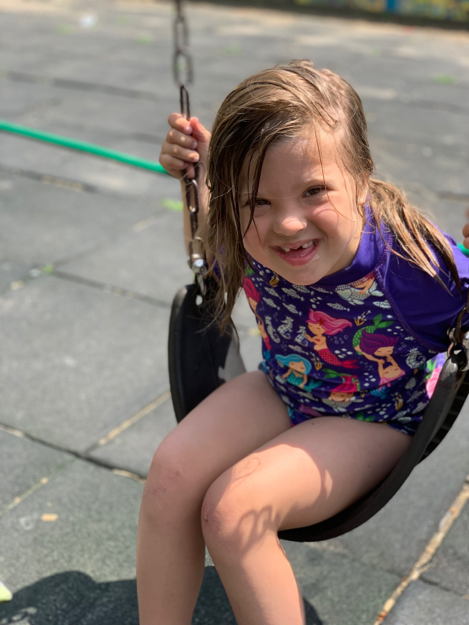 young girl with Down syndrome in a bathing suit on a swing