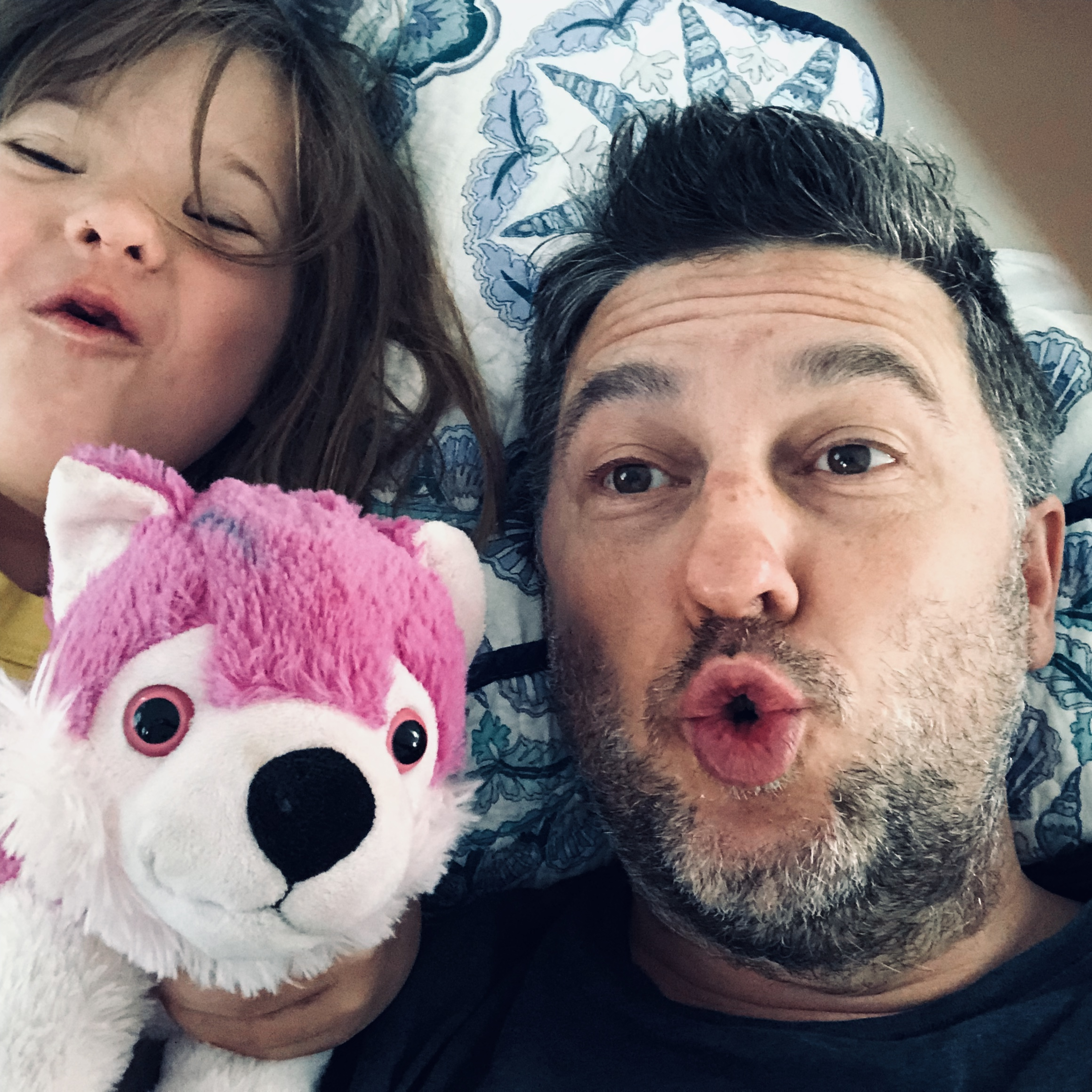 young girl with older man laying down with a white and pink stuffed animal