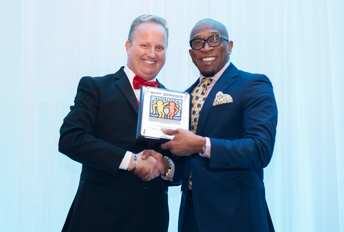 Two Men Holding Best Buddies Excellence Award Plaque