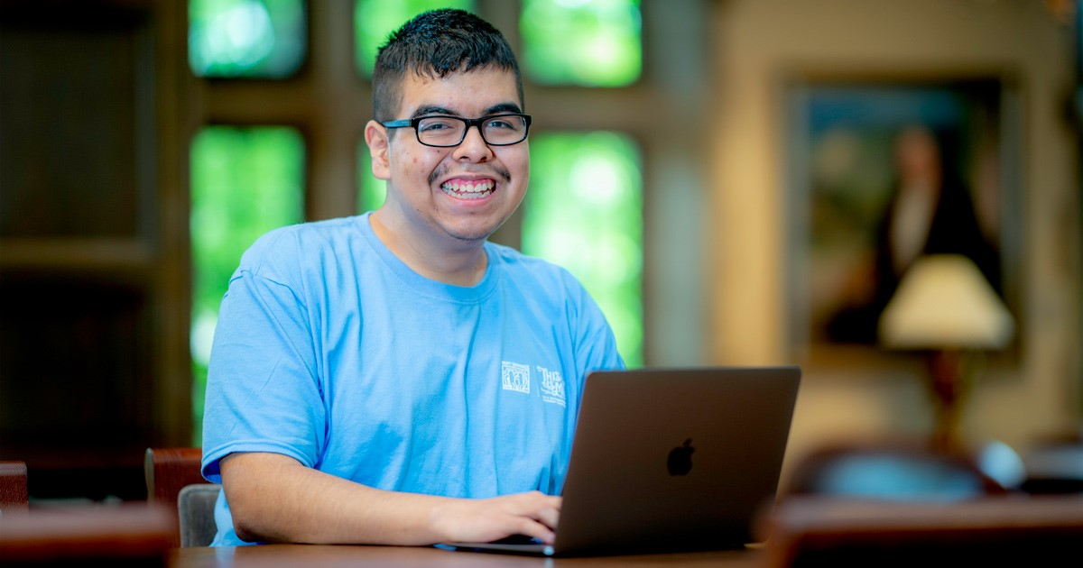 young man smiling using a laptop