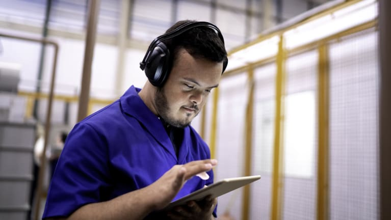 A jobs participant involved with The Society for Human Resource Management (SHRM), SHRM Foundation, and the Entertainment Industry Foundation is employed at his job wearing earphones and working with a digital tablet.