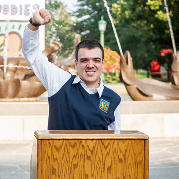 A Best Buddies Leadership Development participant speaks from a wooden podium.