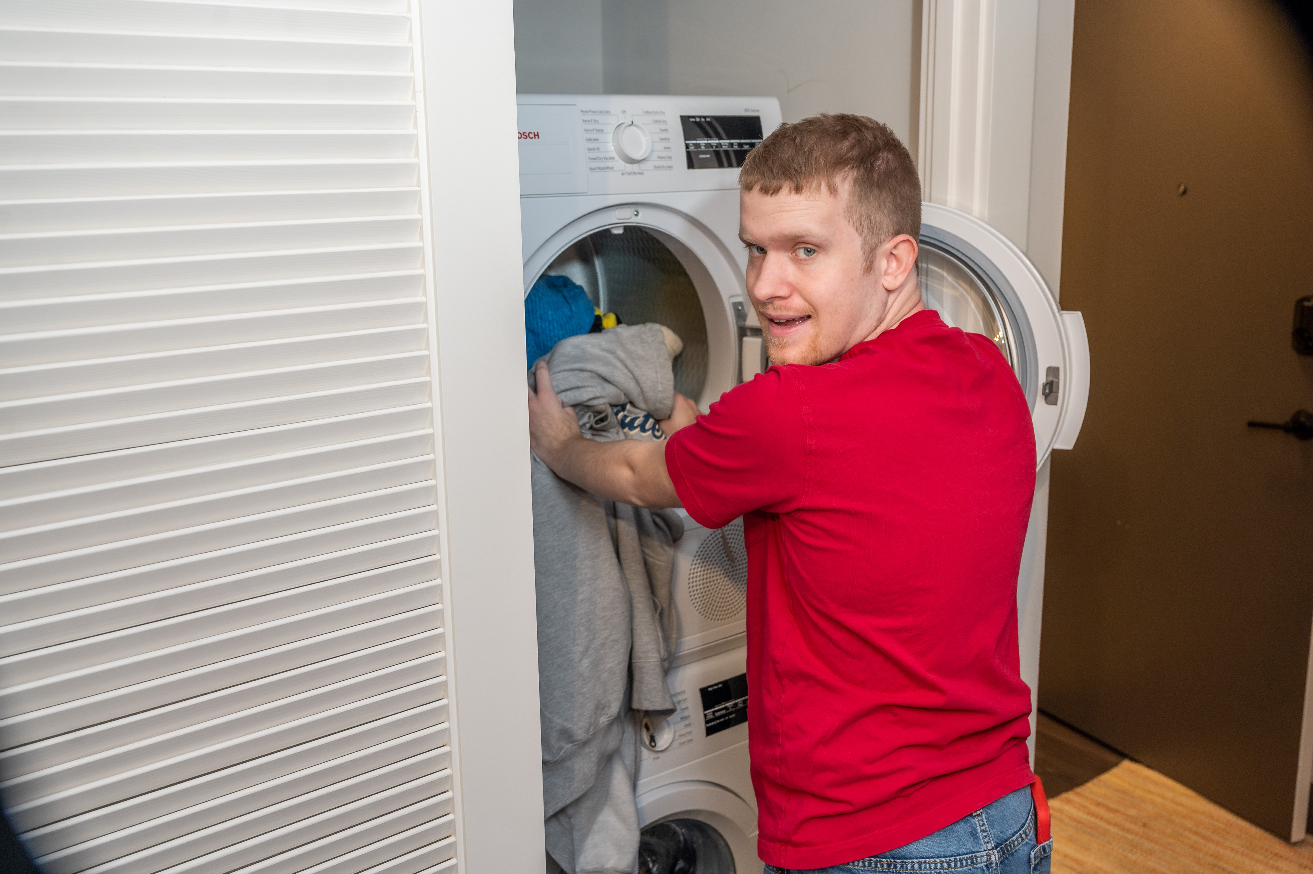 A Best Buddies Living participant does a load of laundry in his co-living apartment.