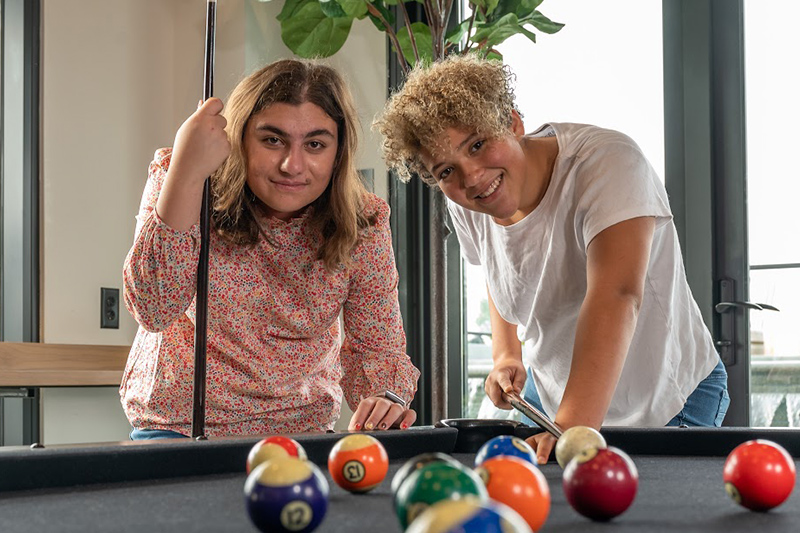 Two female Best Buddies Living participants playing pool
