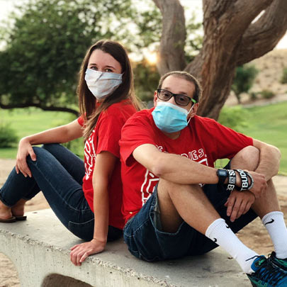 Two Best Buddies Participants sitting next to each other in masks