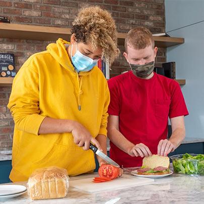 Best Buddies Living participants in masks making sandwiches in their kitchen