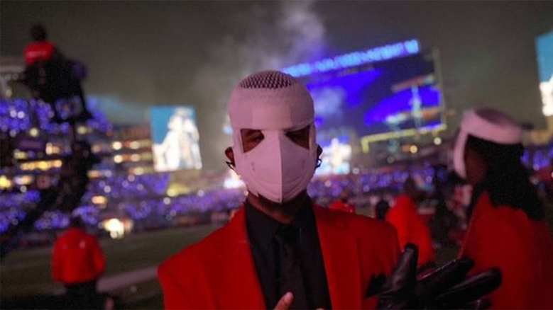Best Buddies Global Ambassador Joshua Felder, performs as a backup dancer for the Weeknd during the Super Bowl 55 halftime show. He is wearing a red jacket with a white mask.