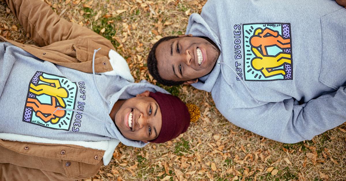 Two African American teenagers smiling in Best Buddies hoodies