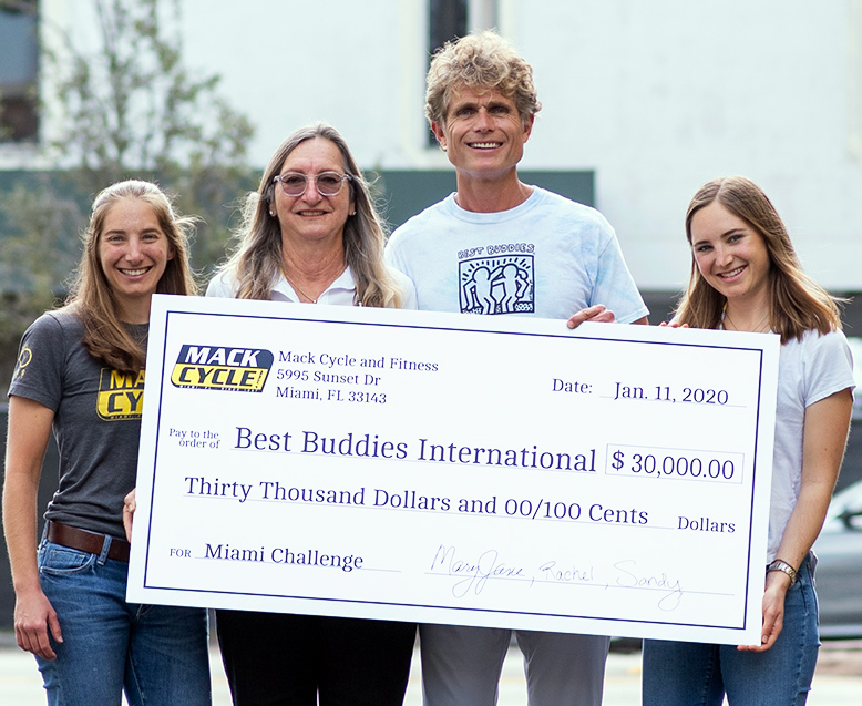 Anthony Shriver, Founder of Best Buddies International, holds a large presentation check for $30,000 dollars. The owner and her two daughters are standing next to him.