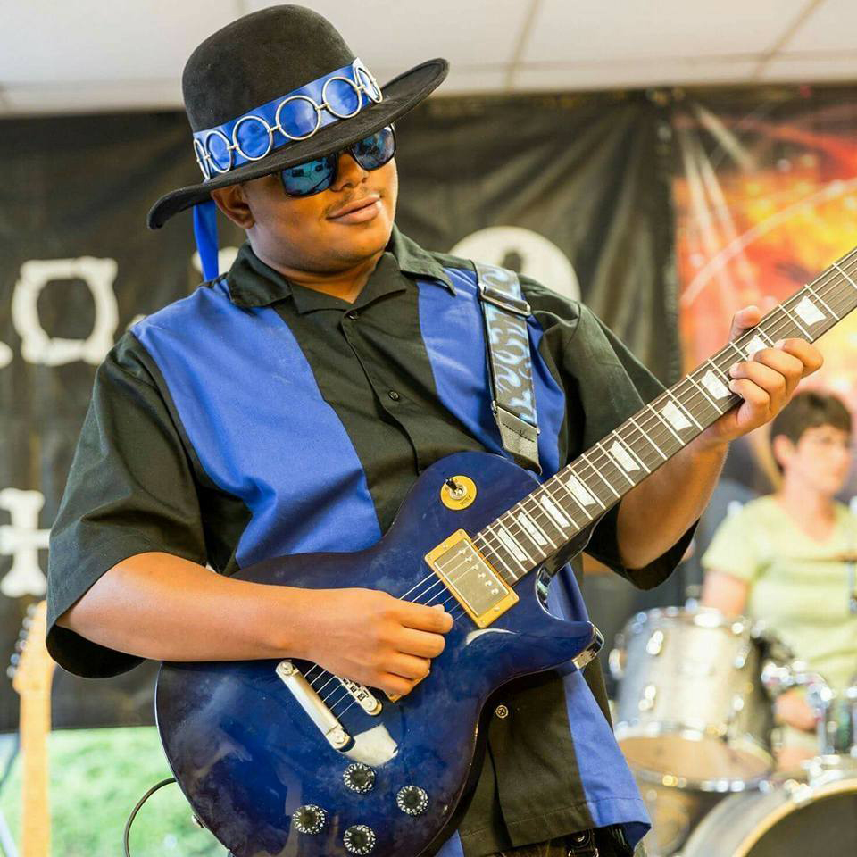 Best Buddies in Ohio Ambassador Participant Zayne Harshow playing his guitar