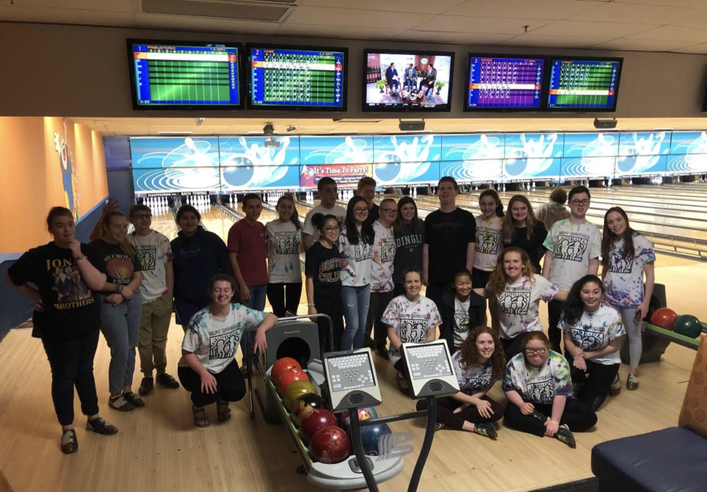 large group of Best Buddies members smile together at a bowling alley