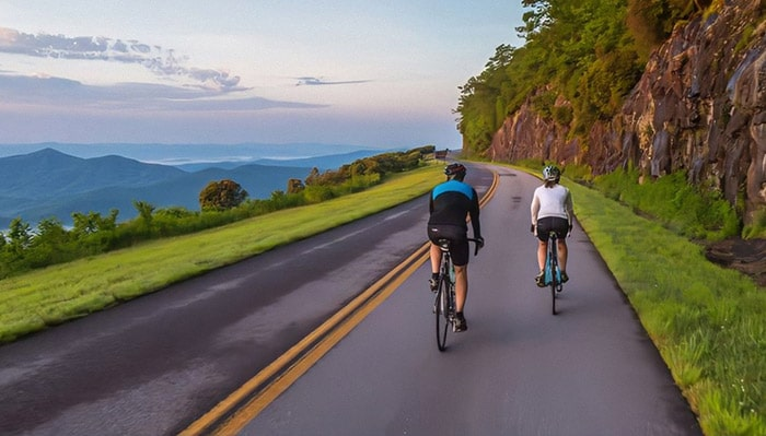 Best Buddies Breakaway Camp: Asheville. Two riders ride on a paved road in the Blue Ridge Mountains.