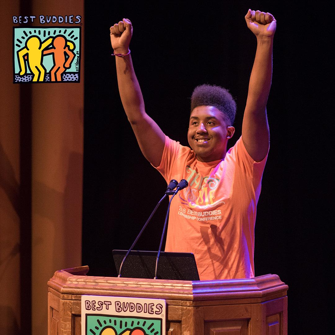 Buddy Ambassador Joshua Felder at a podium with his hands raised