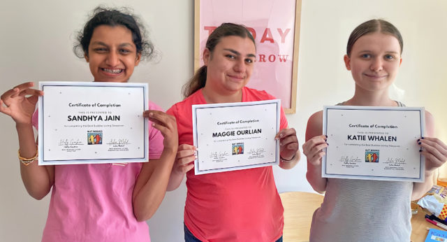 Three girls proudly show their Certificate of Completion for the Best Buddie's Sleepover.