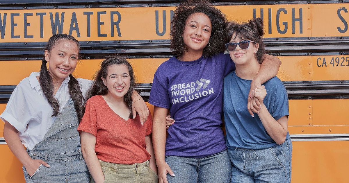 Four teenage females standing in front of a school bus smiling